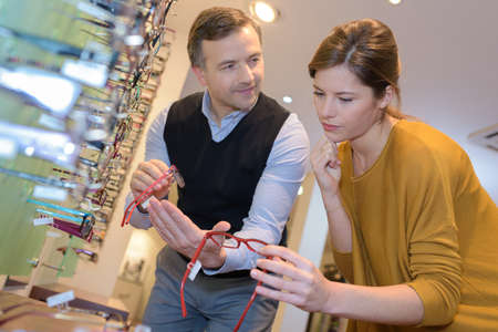 salesgirl: ophthalmologist and beautiful brunette female choosing glasses in optics store