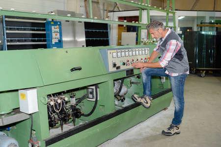 machinery machine: Man setting up factory machinery Stock Photo