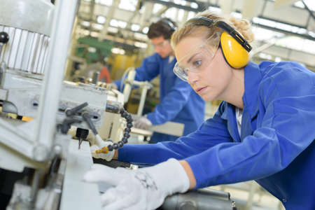 Woman using industrial machine Standard-Bild