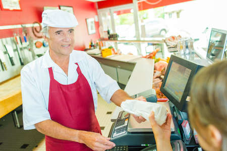 congenial: Butcher passing package to customer