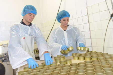 factory workers preparing tins for canned food 스톡 콘텐츠