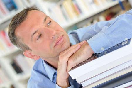 man resting on books Stock Photo