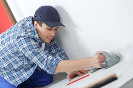 male carpenter sets the baseboard on the floor Stock Photo