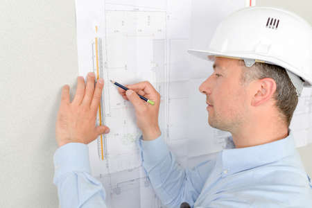 amend: Man measuring plans pinned to wall