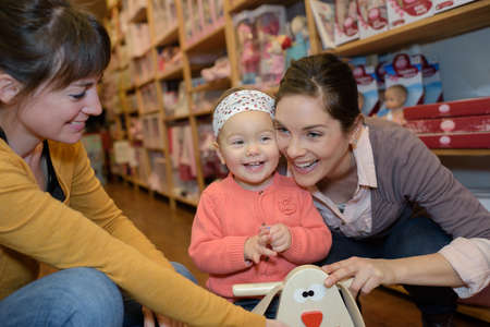 buying: mothers and daughter buying toys Stock Photo