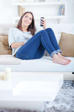 piedi nudi di bambine: La signora sedeva sul divano che teneva cellulare, guardando la distanza Archivio Fotografico