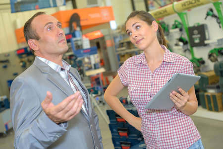 Woman with tablet with nonchalant man Stock Photo