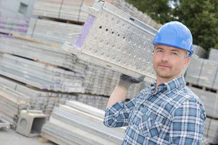 laborer: laborer carrying an aluminum frame Stock Photo