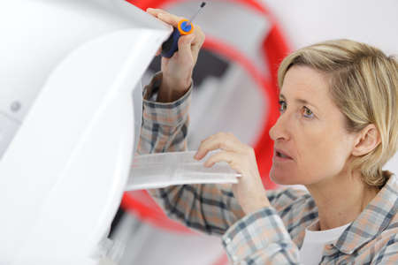 handywoman: blonde handywoman cleaning fixing ventilation system Stock Photo