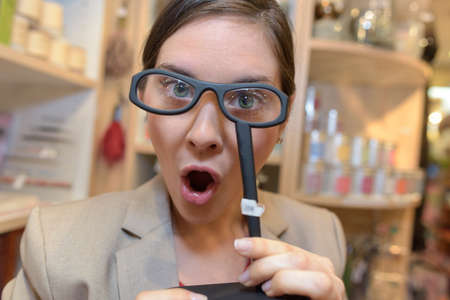 attempt: female client trying magnifying glasses at retail store