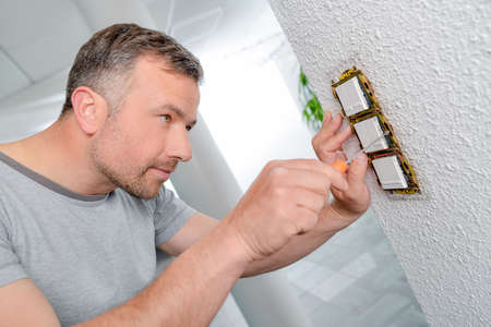 switches: Man screwing row of three switches to wall Stock Photo