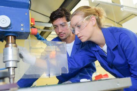 L'homme et la femme à l'aide perçeuse industrielle Banque d'images