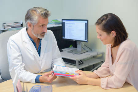 printed matter: Doctor giving printed matter to patient