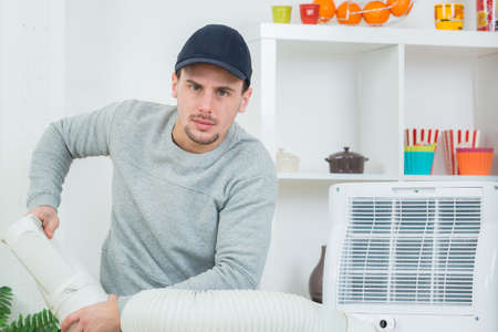 fettler: young technician installing air conditioning system indoors