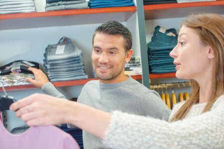 coathanger: Young couple in a garment shop Stock Photo