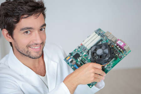 motherboard: Portrait of man holding computer component