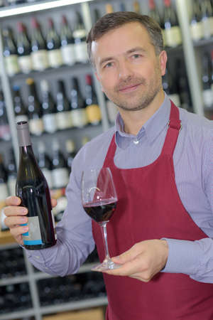 wine merchant showing bottle and glass of wine Stock Photo