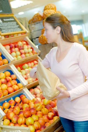 company person: Lady buying nectarines, holding paper bag Stock Photo