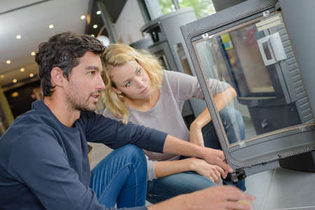 woodburner: Couple looking at a woodburner in a store Stock Photo