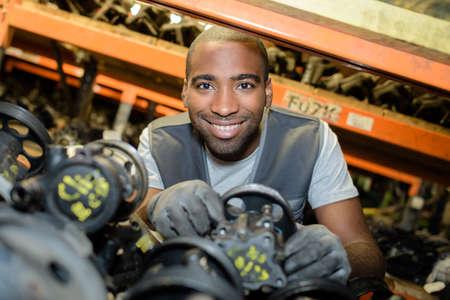 Portrait of man amongst second hand car parts