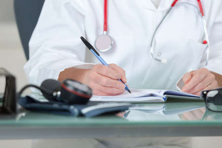 physician writing prescription-cropped image Stock Photo
