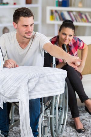 handsome handicapped man in wheelchair watching tv with his girlfriend Stock Photo