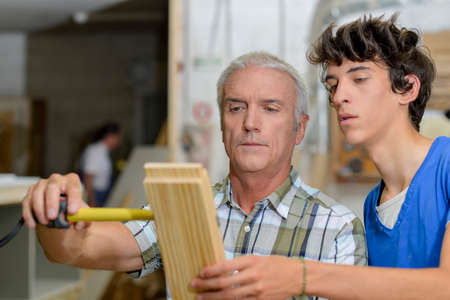 tongue and groove: Carpenter with apprentice, measuring wood Stock Photo