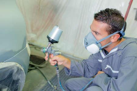refurbish: Mechanic respraying car bodywork