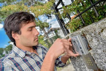 screwing: Man screwing cover back on exterior intercom
