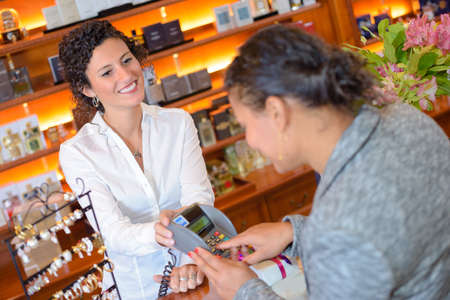 transact: woman buying a perfume Stock Photo