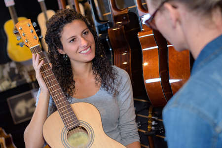 shop assistant: Shop assistant showing guitar to customer