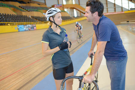 competitive sport: Trainer talking to indoor cyclist Stock Photo