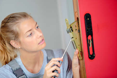 Lady fitting lock into door