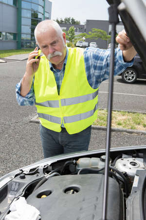 frustrating: senior man on the phone looking at his broken car Stock Photo