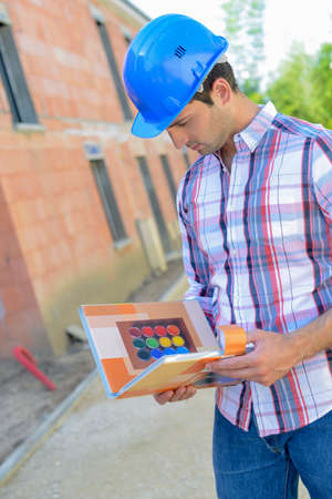 Architect checking colour options on site Stock Photo