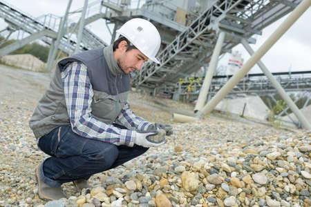 Man examining stones in quarry Stock Photo