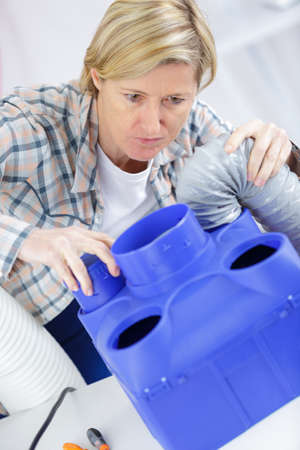 humidify: blonde woman installing new ac system
