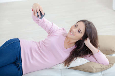 Lady layed on sofa taking photo of herself Stock Photo
