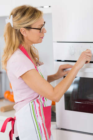 housewife mother setting the oven to cook meal