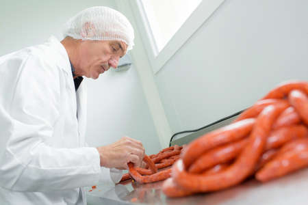 Butcher making sausages Stock Photo