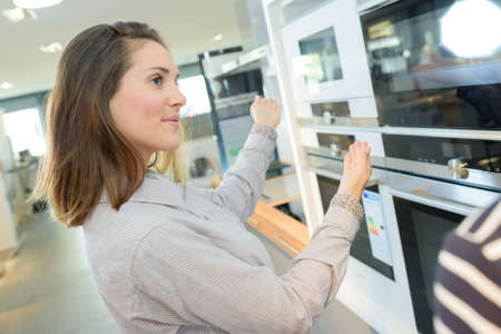 gamme de produit: customer looking at built-in ovens in domestic appliances shop