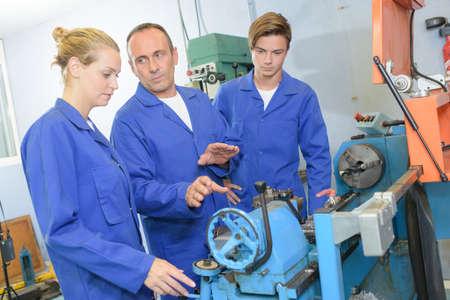 trainees: Tutor instructing trainees regarding machinery Stock Photo