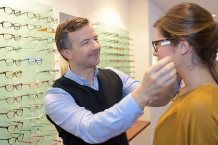 Optician fitting eyeglasses onto customer