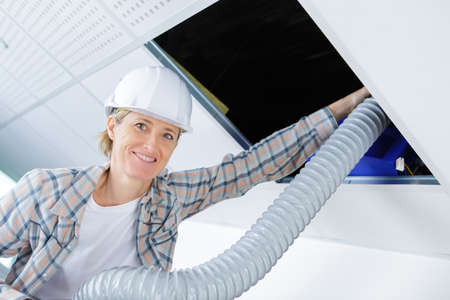 wireman: female elctrician fitting air conditions pipe in building ceiling Stock Photo