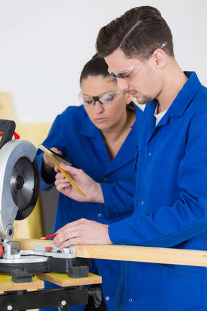 traineeship: young apprentice with professional carpenter