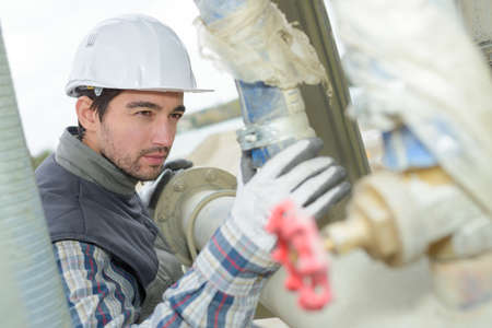 pipework: Man inspecting industrial pipework
