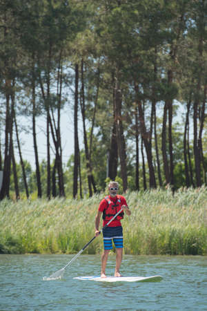 soft pedal: man enjoying a ride on the lake with paddleboard Stock Photo