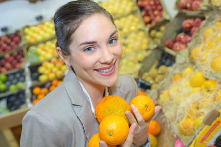 pretty woman buying fresh fruits and vegetables at food-store