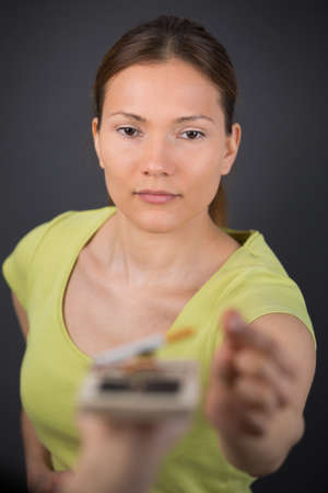 woman reaching for cigarette in a mousetrap