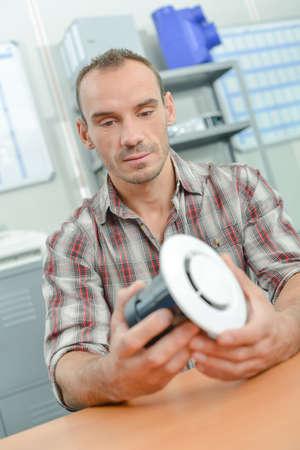 Handyman holding a part Stock Photo